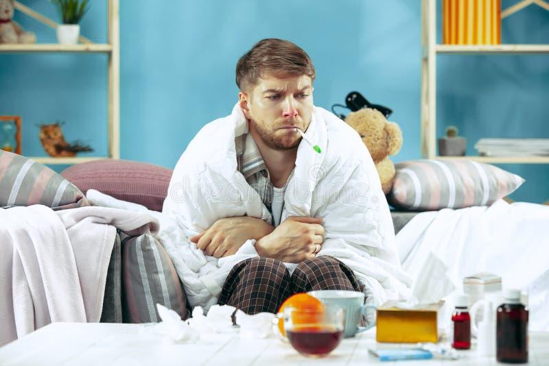 Uomo malato barbuto con il condotto di scarico che si siede sul sofà a casa Malattia, influenza, concetto di dolore Rilassamento  immagine stock