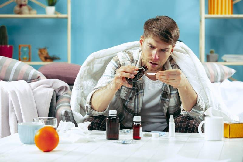 Uomo malato barbuto con il condotto di scarico che si siede sul sofà a casa Malattia, influenza, concetto di dolore Rilassamento  fotografia stock libera da diritti