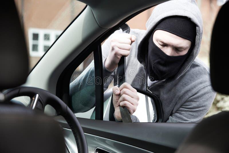 Uomo mascherato che si rompe nell'automobile con il bastone a leva fotografie stock