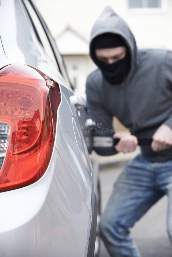 Uomo mascherato che si rompe nell'automobile con il bastone a leva fotografia stock libera da diritti