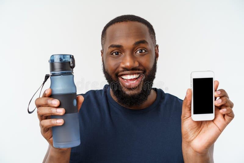 Uomo maschio afroamericano di sport dell'atleta con eseguire gli sport con il telefono cellulare e l'acqua potabile dalla bottigl immagini stock libere da diritti