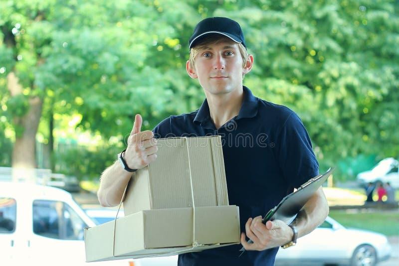Uomo maschio sorridente del corriere di distribuzione postale all'aperto fotografia stock