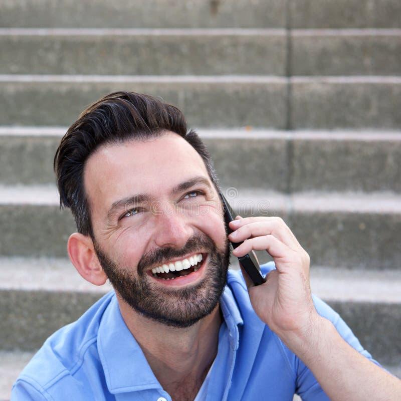 Uomo maturo allegro che usando cellulare e risata fotografia stock