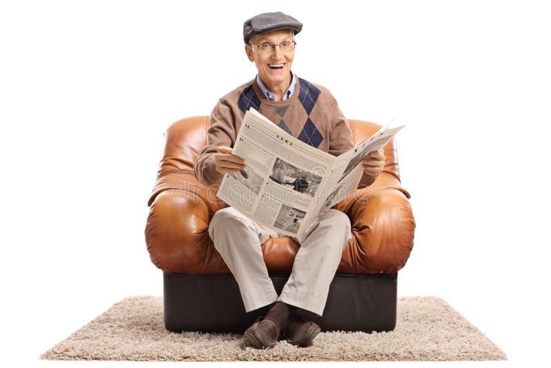 Uomo maturo allegro con il giornale che si siede in poltrona di cuoio immagini stock