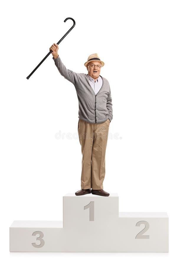 Uomo maturo allegro con una canna che sta su un piedistallo dei vincitori fotografia stock libera da diritti