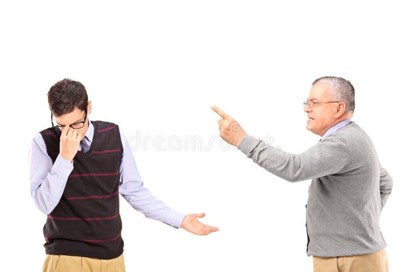 Uomo maturo arrabbiato che ha una discussione con un più giovane uomo di ribaltamento fotografia stock libera da diritti