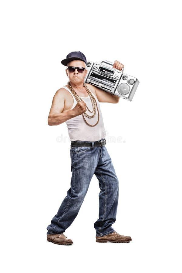 Uomo maturo in attrezzatura hip-hop che tiene un artificiere del ghetto fotografia stock