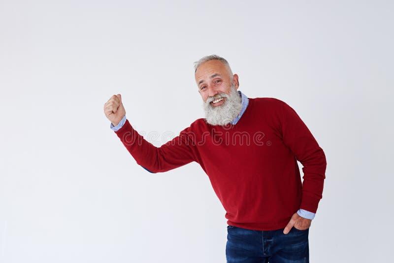 Uomo maturo barbuto schietto che alza Hans e che esamina macchina fotografica fotografie stock