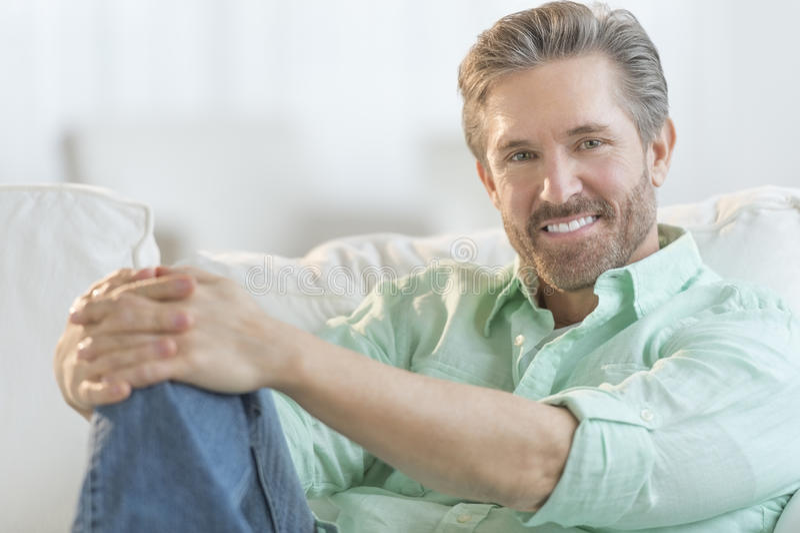 Uomo maturo bello che si rilassa sul sofà immagini stock libere da diritti