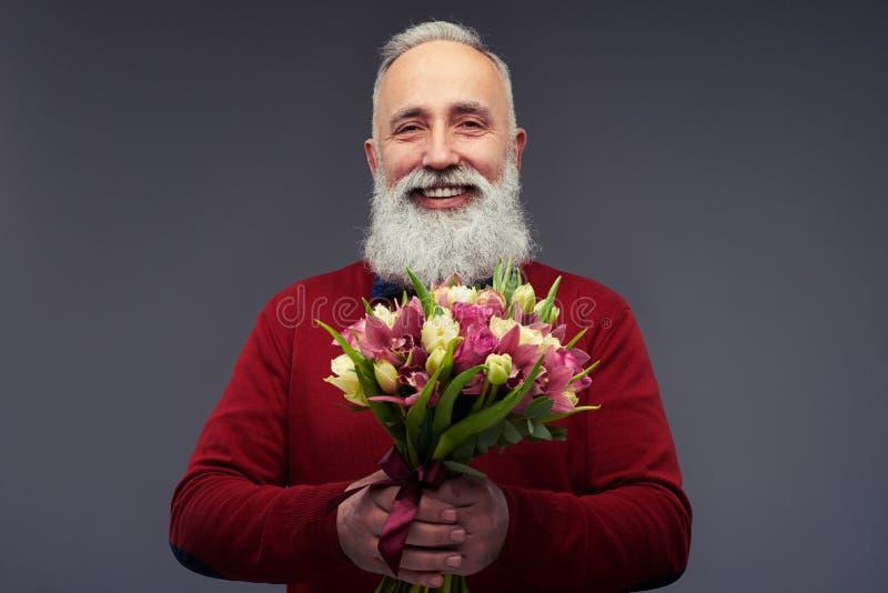 Uomo maturo bello con il mazzo grigio della tenuta della barba di fotografie stock