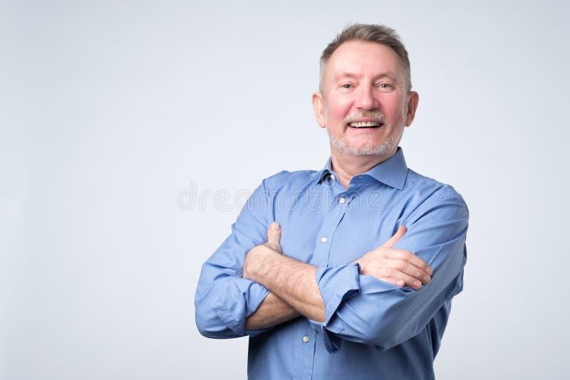 Uomo maturo bello sicuro in vestito casuale che esamina macchina fotografica e sorridere immagine stock