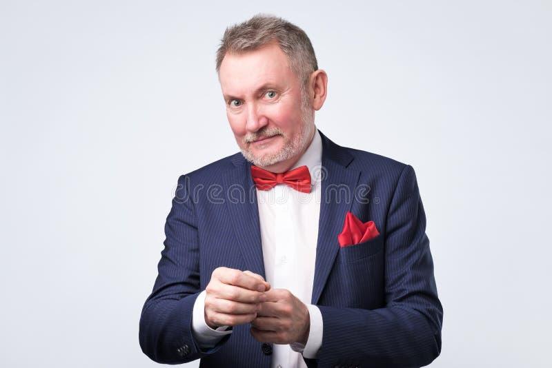 Uomo maturo bello sicuro in vestito casuale che esamina macchina fotografica e sorridere fotografia stock
