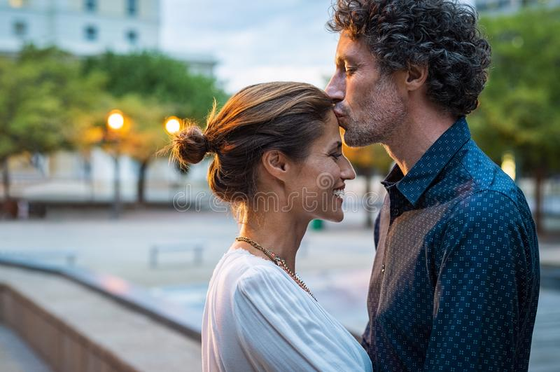Uomo maturo che bacia donna sulla fronte fotografie stock