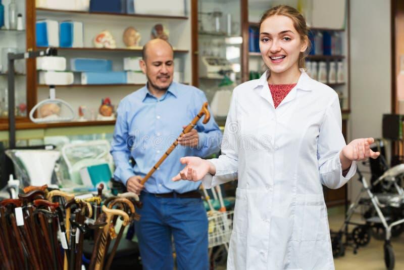 Uomo maturo che chiede a medico femminile positivo amichevole riguardo alla camminata fotografia stock