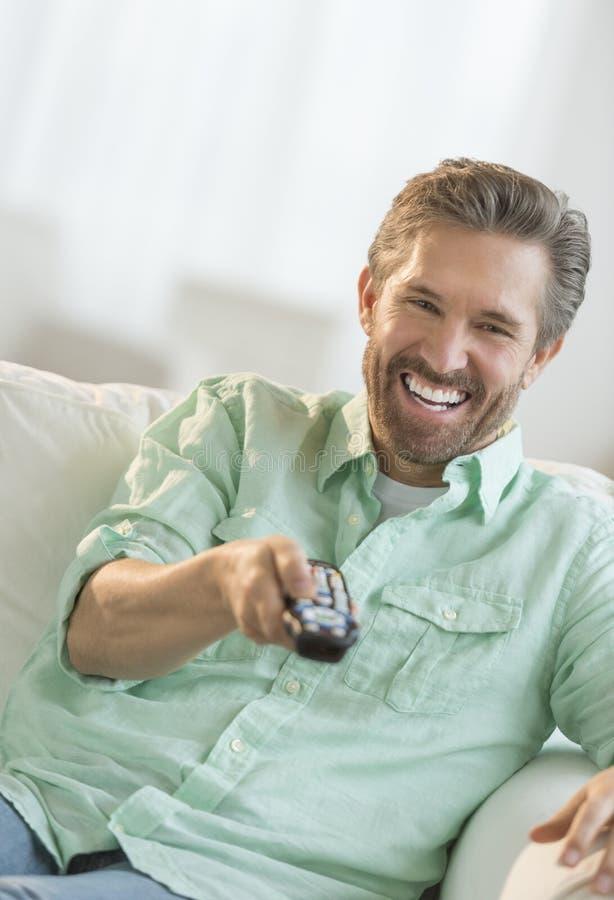 Uomo maturo che guarda TV sul sofà fotografia stock libera da diritti