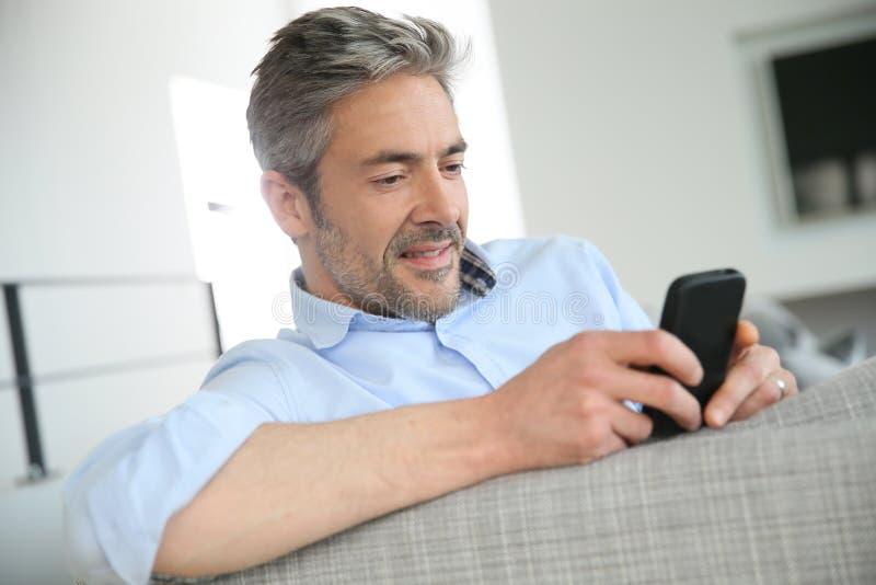 Uomo maturo che invia gli sms con lo smartphone fotografia stock libera da diritti