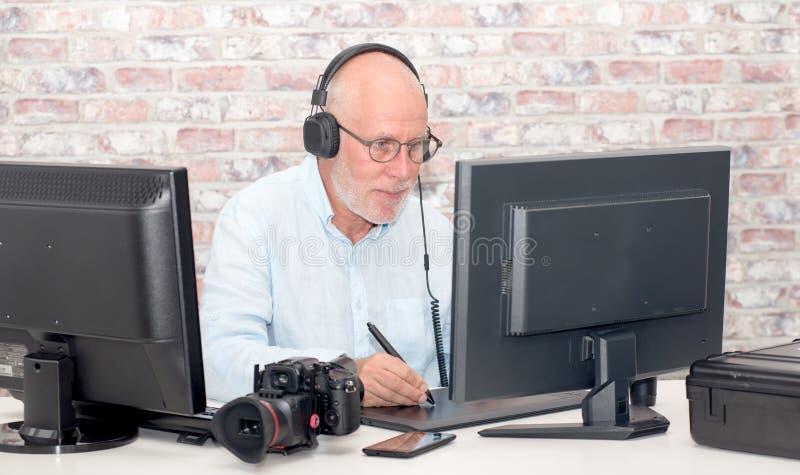 Uomo maturo che lavora alla sua tavola dei grafici immagini stock