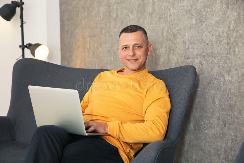 Uomo maturo che lavora con il computer portatile sul sof? fotografia stock