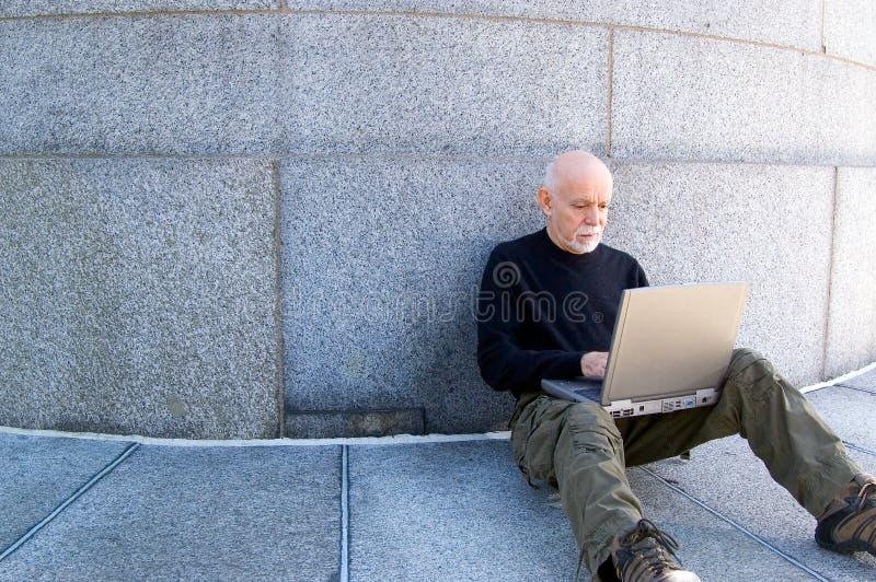 Uomo maturo che per mezzo di un calcolatore fotografia stock libera da diritti