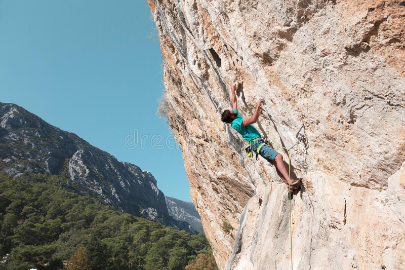 Uomo maturo che scala alta roccia che rompe i limiti immagine stock