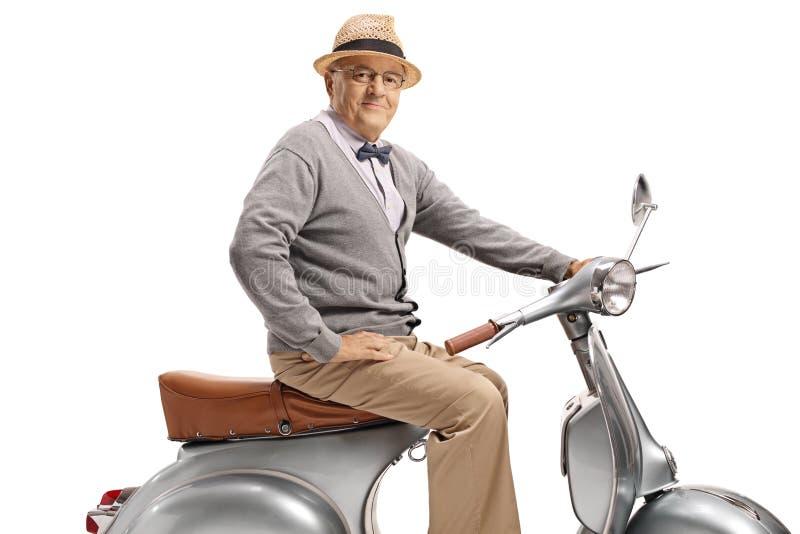 Uomo maturo che si siede su un motorino d'annata immagini stock libere da diritti