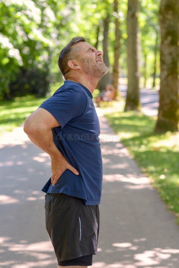 Uomo maturo che tiene la sua parte posteriore dolorosa dopo avere corso fotografia stock libera da diritti