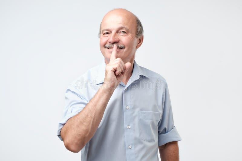 Uomo maturo con il dito sulle labbra che chiede il silenzio immagini stock