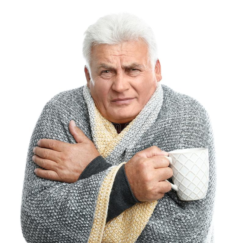 Uomo maturo con tazza di bevande calde che soffre di freddo sullo sfondo fotografia stock libera da diritti