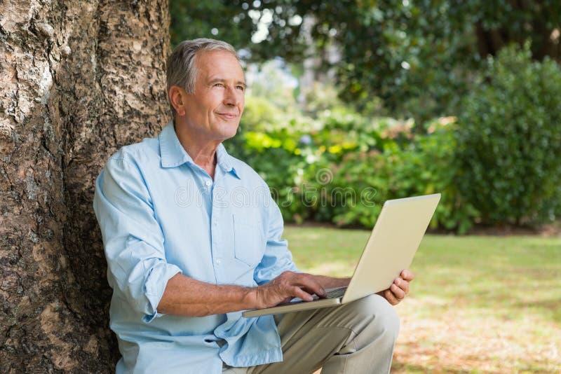 Uomo maturo con un computer portatile che esamina il cielo immagini stock