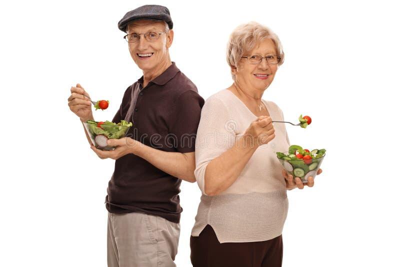 Uomo maturo e donna che mangiano le insalate fotografia stock