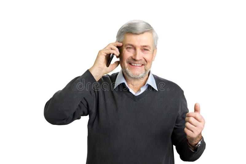 Uomo maturo emozionante che parla sul telefono immagini stock