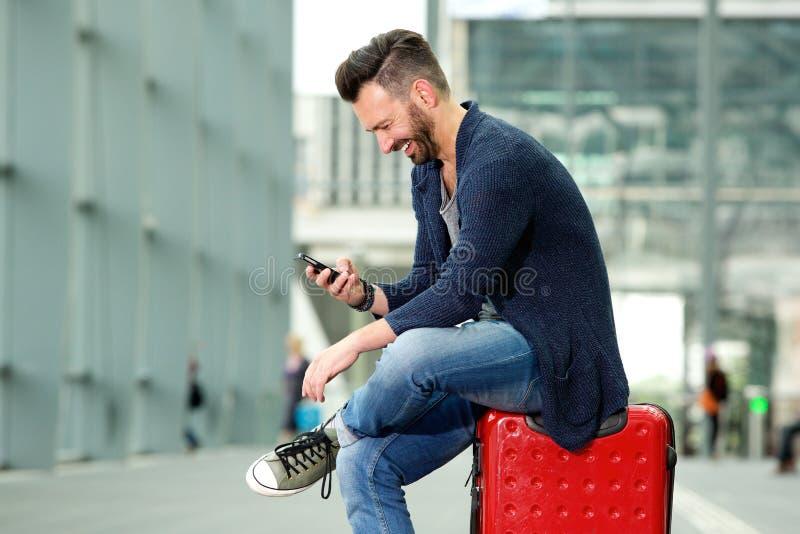 Uomo maturo felice che si siede esaminare e sulla borsa di viaggio telefono cellulare immagini stock libere da diritti