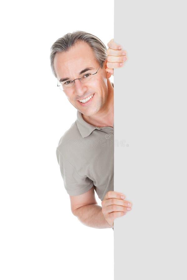 Uomo maturo felice che sta dietro il cartello immagini stock libere da diritti