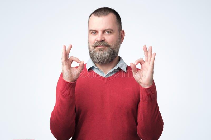 Uomo maturo nel segno GIUSTO di rappresentazione rossa del maglione fotografie stock libere da diritti