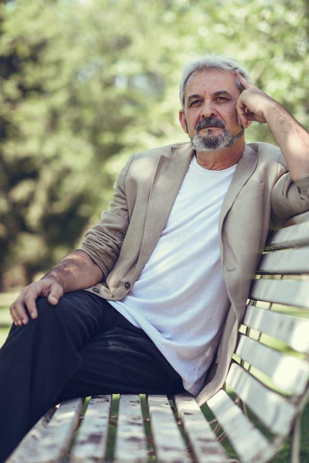Uomo maturo pensieroso che si siede sul banco in un parco urbano immagine stock