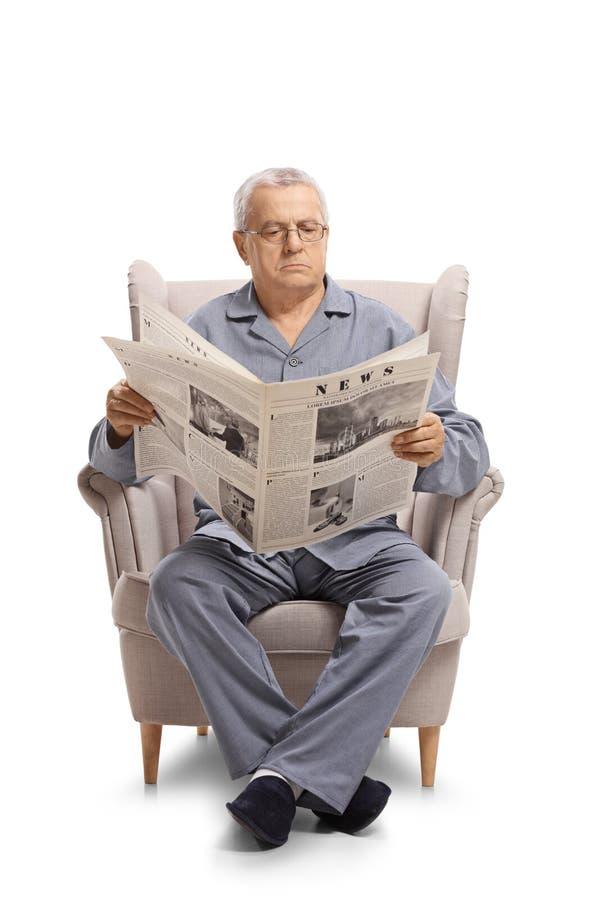 Uomo maturo in pigiami che si siedono in una poltrona e che leggono un newsp fotografia stock