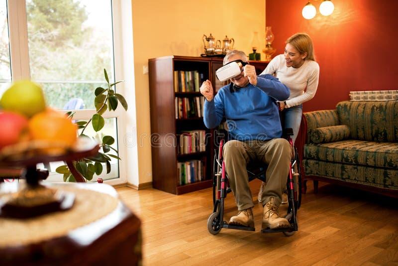 Uomo maturo in sedia a rotelle che gioca il gioco della corsa con VR immagine stock