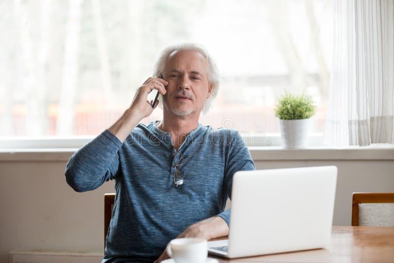 Uomo maturo senior che parla sul telefono che fa chiamata a casa immagini stock libere da diritti