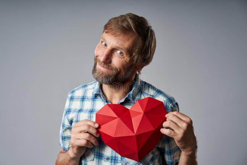 Uomo maturo sorridente in camicia a quadretti che tiene forma del cuore immagini stock