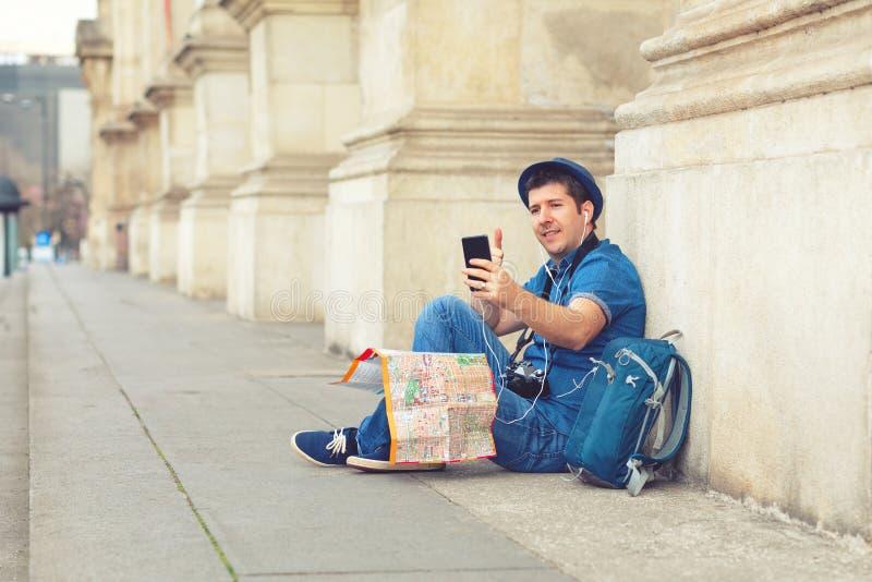 Uomo maturo sorridente facendo uso del telefono cellulare mentre sedendosi contro selfie di presa turistico felice del †di c immagine stock libera da diritti