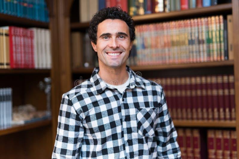 Uomo maturo sorridente in una biblioteca immagini stock libere da diritti