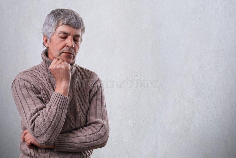 Uomo maturo triste pensieroso che tiene la sua mano sotto il suo mento che guarda giù con l'espressione infelice che pensa a qual immagini stock libere da diritti