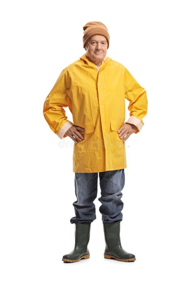 Uomo maturo in un impermeabile giallo immagini stock libere da diritti