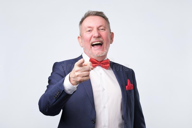 Uomo maturo in vestito blu che indica dito e sorriso a trentadue denti Colpo dello studio fotografia stock libera da diritti