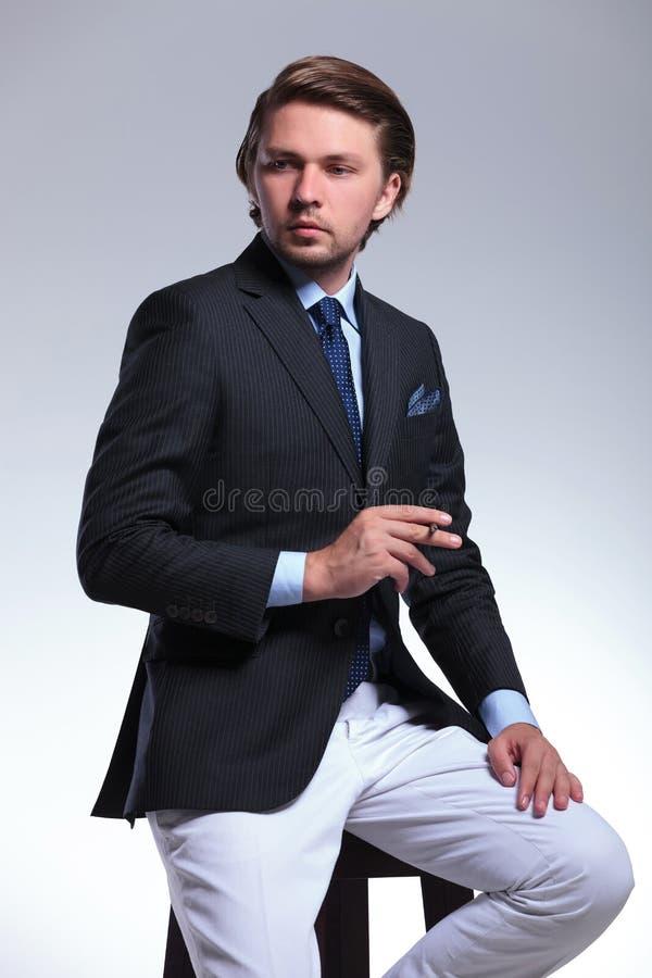 Uomo messo di affari con la sigaretta a disposizione immagine stock