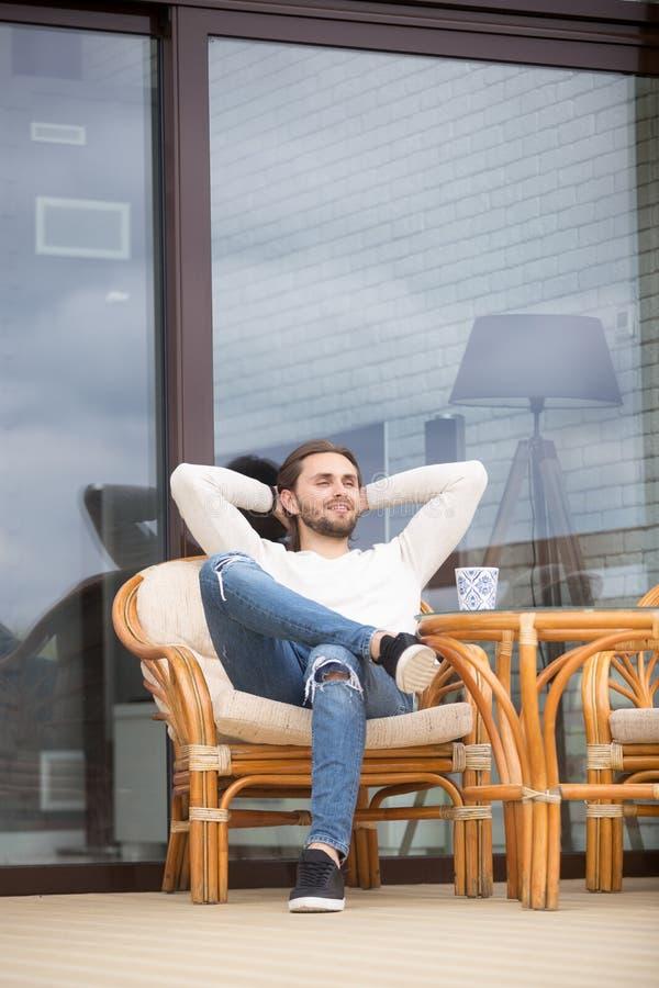 Uomo millenario positivo che si siede sulla poltrona di aria aperta a casa immagini stock libere da diritti
