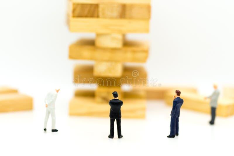 Uomo miniatura: Uomo d'affari del gruppo ed alto blocco di legno Uso di immagine per il rischio nell'affare, vendita, concetto di fotografia stock libera da diritti