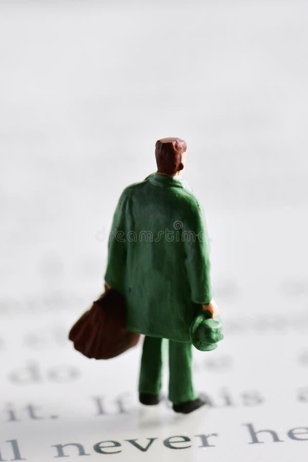 Uomo miniatura del viaggiatore su un lettore del libro elettronico fotografie stock libere da diritti