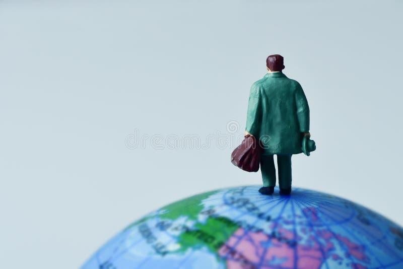Uomo miniatura del viaggiatore sul globo terrestre fotografia stock libera da diritti