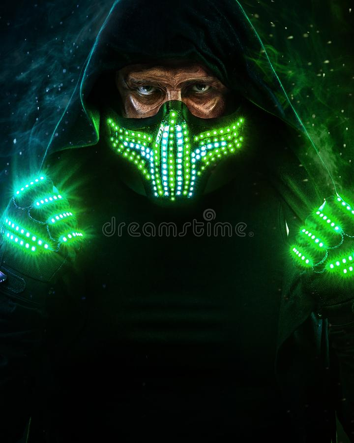Uomo misterioso nell'usura nera, nella maschera al neon ed in guanti Pastore o stregone del carattere in abito a partire dal futu fotografia stock